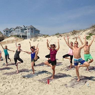 group of students doing a standing yoga pose on the beach during an outer banks beach yoga class