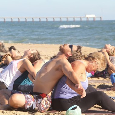 yoga students pairing together for yoga poses on the beach during an outer banks beach yoga class
