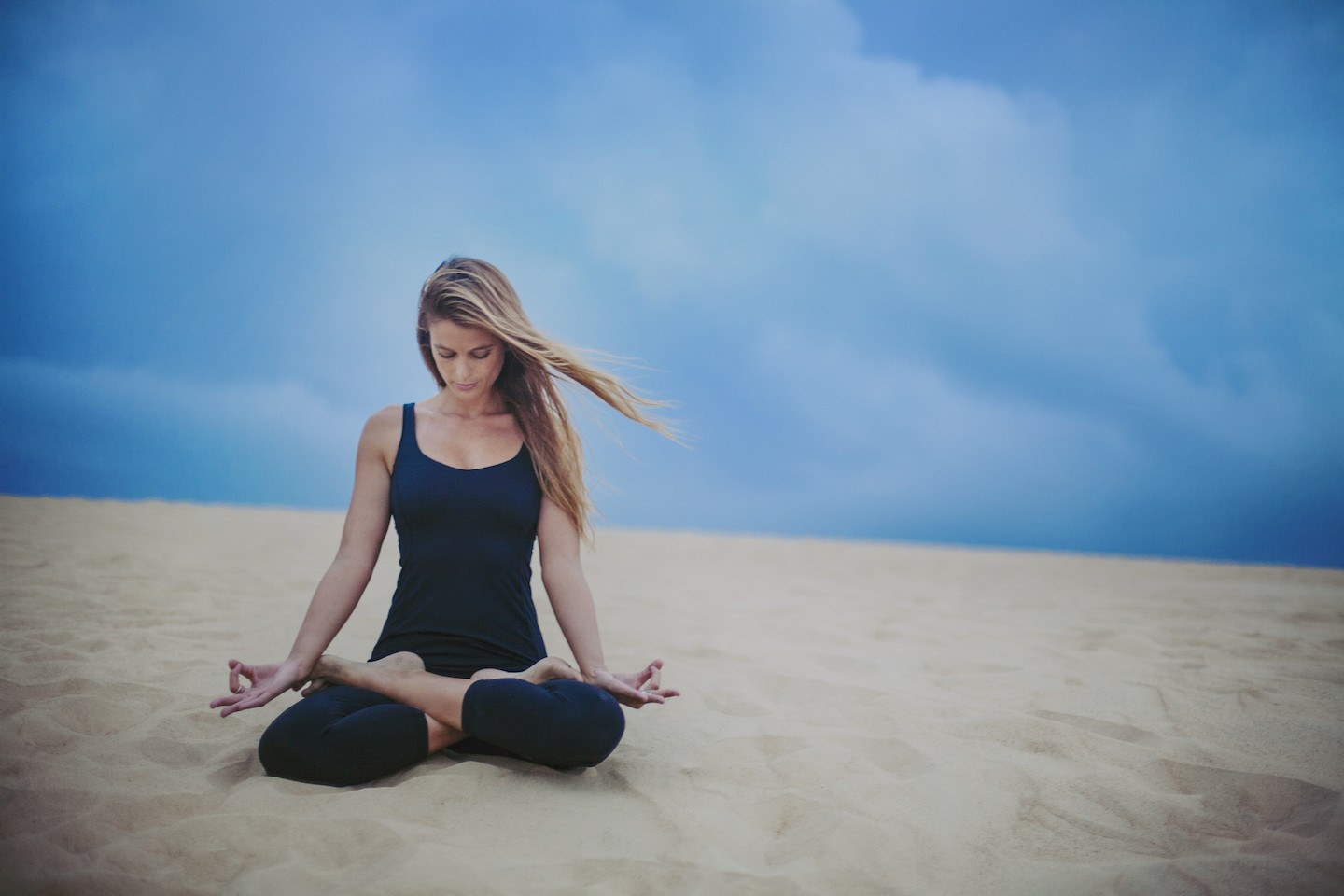 duck village yoga studio instructor doing sitting meditation yoga pose in sand on the outer banks